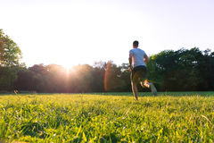 A handsome young man running during sunset in a park Stock Photos