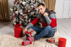 Handsome young man with a scarf sitting with gifts on plaid near the Christmas tree stock images
