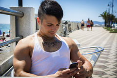 Handsome young man at the seaside sitting and using cell phone. Handsome muscular young man at the seaside sitting and using cell phone in summer Royalty Free Stock Photo
