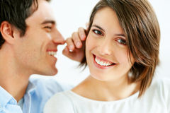 Handsome young man sharing secrets with his wife Stock Photos