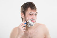 Handsome young man with a shaving foam Royalty Free Stock Images
