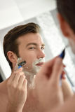 Handsome young man shaving in front of mirror Royalty Free Stock Images