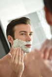 Handsome young man shaving in front of mirror stock photography