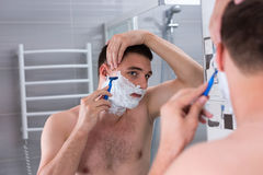 Handsome young man shaving his face with a razer and looking at Royalty Free Stock Photos