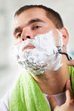 Handsome young man is shaving his face Stock Photography