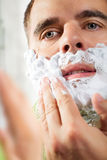 Handsome young man is shaving his face Stock Photos