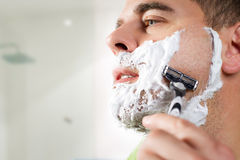 Handsome young man is shaving his face Royalty Free Stock Image