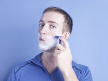 Handsome young man shaving. With a razor blue Stock Images