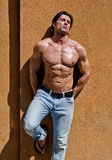 Handsome young man shirtless with jeans against a wall, eyes closed Stock Image