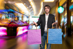 Handsome young man with shopping bags in shopping mall Royalty Free Stock Photography