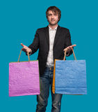 Handsome young man with shopping bags in shopping mall Stock Image