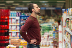 Handsome Young Man Shopping In A Grocery Supermarket Royalty Free Stock Photos