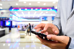 Handsome young man in shopping mall using mobile Phone. Stock Image