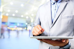 Handsome young man in shopping mall using mobile tablet Royalty Free Stock Photos