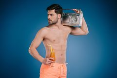 Handsome young man in shorts holding tape recorder and glass of summer cocktail. On blue Stock Images