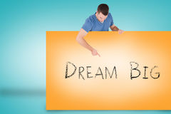Handsome young man showing card with dream big Royalty Free Stock Images