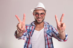 Handsome young man showing the victory sign. Royalty Free Stock Photo