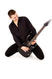 The handsome young man sits and plays the electric guitar Royalty Free Stock Photo