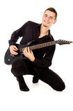 The handsome young man sits and plays the electric guitar Stock Image