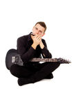 The handsome young man sits plays the electric guitar and harmon Stock Photos