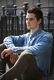 Handsome young man sitting against handrail outdoors Stock Images
