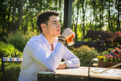 Handsome young man sitting alone at table outside. In park or nature, with glass of soda beverage Stock Photos