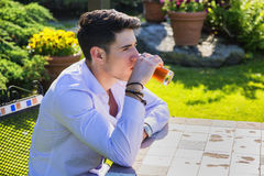 Handsome young man sitting alone at table outside Royalty Free Stock Image