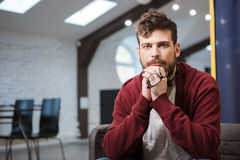 Handsome young man is sitting ang holding glasses Royalty Free Stock Photography