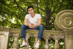 Handsome young man sitting on a balcony or bridge Royalty Free Stock Photo