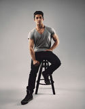 Handsome young man sitting on bar stool Stock Photo