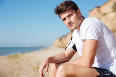 Handsome young man sitting on the beach Stock Photography