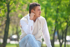 Handsome young man sitting on a bench Royalty Free Stock Image