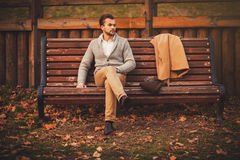 Handsome young man sitting on the bench Stock Photography