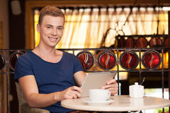 Handsome young man sitting in cafe. Royalty Free Stock Photos