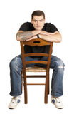 Handsome young man sitting on a chair Royalty Free Stock Photography