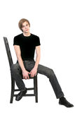 Handsome young man sitting on a chair Royalty Free Stock Images