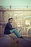 Handsome young man sitting in the city center royalty free stock photo