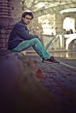 Handsome young man sitting in the city center stock image