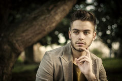 Handsome young man sitting in city park Stock Image