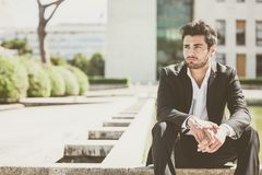 Handsome young man sitting in the city Royalty Free Stock Image