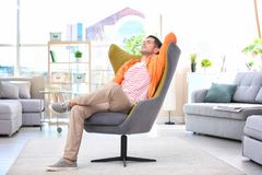 Handsome young man sitting in comfortable armchair. At home Royalty Free Stock Image