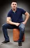 Handsome young man sitting down Stock Image