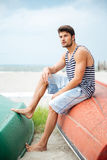 Handsome young man sitting on a fishing boat by sea Stock Photo