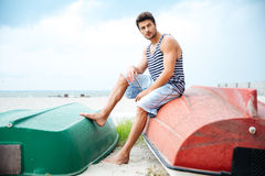 Handsome young man sitting on a fishing boat by sea Royalty Free Stock Image
