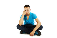 Handsome young man sitting on the floor Stock Photos