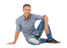 A handsome young man sitting on the floor Royalty Free Stock Images