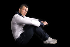 Handsome young man sitting on the floor, arms on his knees Stock Photo