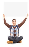 Handsome young man sitting on a floor and holding a white panel. Above his head  on white background Royalty Free Stock Photography