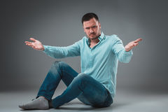 Handsome young man sitting on a floor with raised hands gesturing on gray background Stock Photo