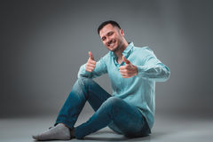 Handsome young man sitting on a floor with raised hands gesturing happiness on gray background Royalty Free Stock Image